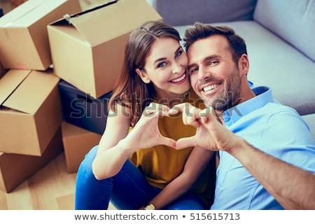 happy couple sitting on floor unpacking boxes stock photo © wavebreak_media