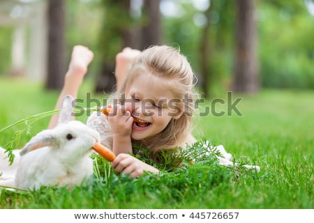 Stock photo: Happy baby girl plays with a carrot