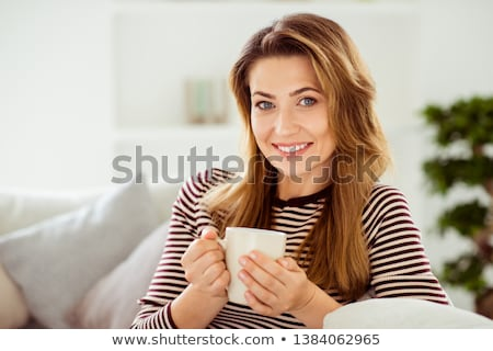 Charming young women sitting on a sofa with cups in a living room stock photo © wavebreak_media