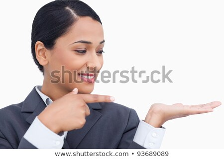 Close up of smiling saleswoman pointing and looking at her palm against a white background stock photo © wavebreak_media