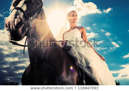 Bride in wedding dress riding a horse, backlit Stock photo © Kzenon