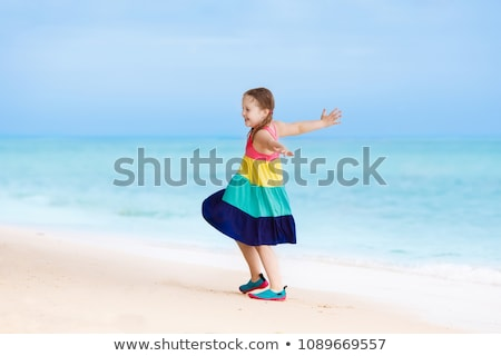 Girl in summer dress digging at beach  Stock photo © bigandt