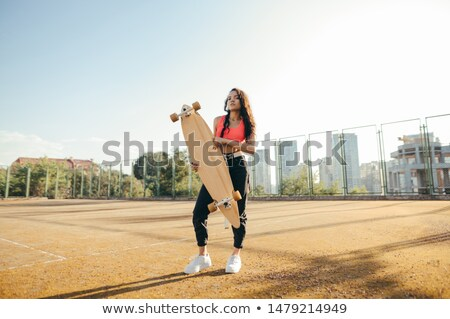 Beautiful young girl with longboard standing on the tennis court Stock photo © vlad_star