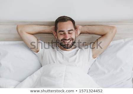 young man lying on bed stock photo © iofoto