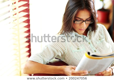 businesswoman reading magazine in modern office stock photo © deandrobot