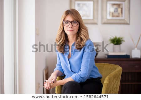 elegant fashion woman sitting on a chair while smiling stock photo © feedough