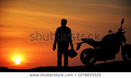 Silhouette of a biker watching a beautiful sunset stock photo © elgusser