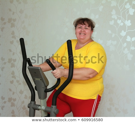 overweight woman exercising on bike simulator  Stock photo © Mikko