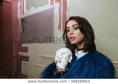 Gorgeous woman at night. Holding artificial skull. Stock photo © deandrobot
