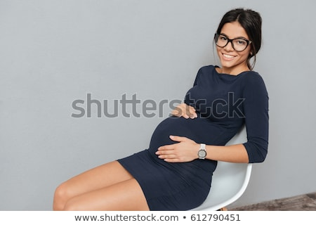 happy pregnant business woman sitting over grey background stock photo © deandrobot