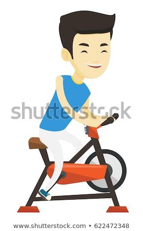 asian man riding stationary exercise bike isolated stock photo © qingwa