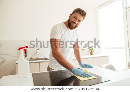 Smiling casual bearded man wipes a stove on kitchen Stock photo © deandrobot