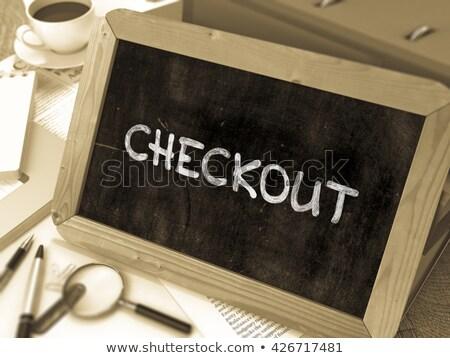checkout handwritten by white chalk on a blackboard stock photo © tashatuvango