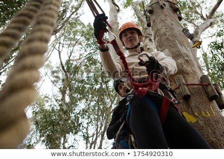 Woman wearing safety helmet fixing carabiner in rope in the forest Stock photo © wavebreak_media