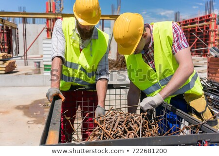 Stock photo: Two workers checking a pile of rusty steel bars