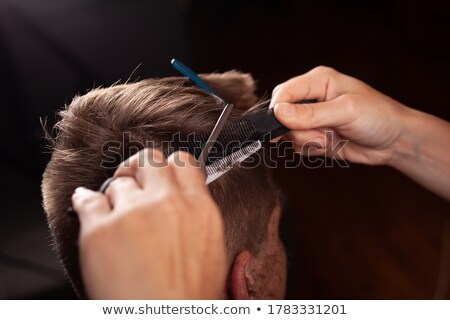 Close-up of the head of a young man and the hands of a hairstylist Stock photo © Kzenon