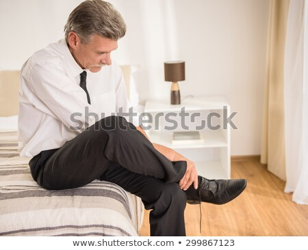 Senior Adult man sitting on hotel bed Stock photo © IS2