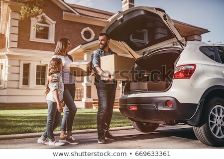 Woman standing by car holding box Stock photo © IS2