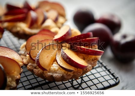 Homemade crumble tarts with fresh plum slices placed on iron baking grill Stock photo © dash