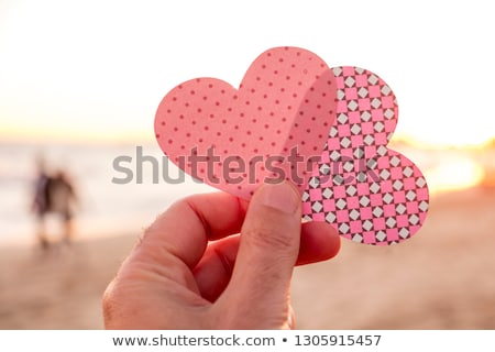 man holding a heart cut at dawn or sunset stock photo © nito