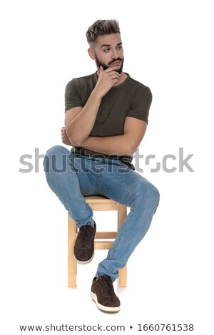 Attractive man holding his hand at his chin while looking at the Stock photo © feedough