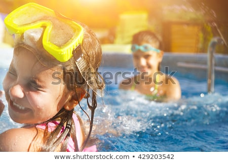 Two cute girls playing in swimming pool stock photo © dashapetrenko