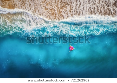Luchtfoto zwemmen vrouw zee zonsondergang jonge vrouw Stockfoto © denbelitsky
