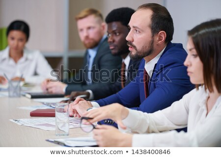 One of young confident brokers talking to colleague at seminar Stock photo © pressmaster