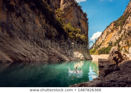 Man jumping into the water of a gorge in the Pyrenees mountains Stock photo © Kzenon