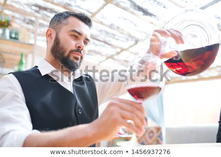 Young bearded barman or sommelier pouring red wine into wineglass Stock photo © pressmaster