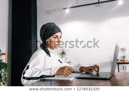 Young muslim student in hijab making working notes by table Stock photo © pressmaster