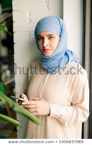 Young casual muslim businesswowman in hijab messaging in smartphone Stock photo © pressmaster