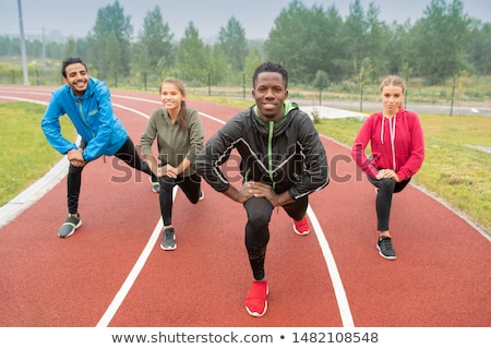 Healthy young intercultural friends in activewear exercising on race tracks Stock photo © pressmaster