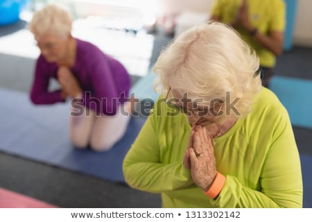 Front view of senior woman doing yoga on the foreground and her friend behind her in fitness studio Stock photo © wavebreak_media