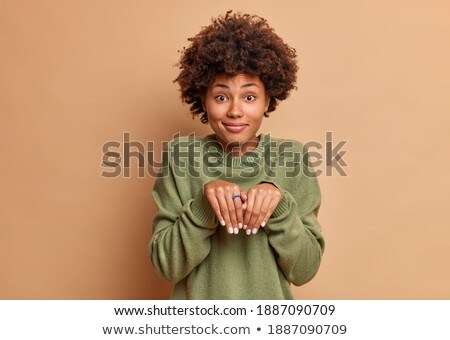 Indoor shot of lovely curly woman with pleasant smile, wears spectacles and white casual jumper, iso Stock photo © vkstudio