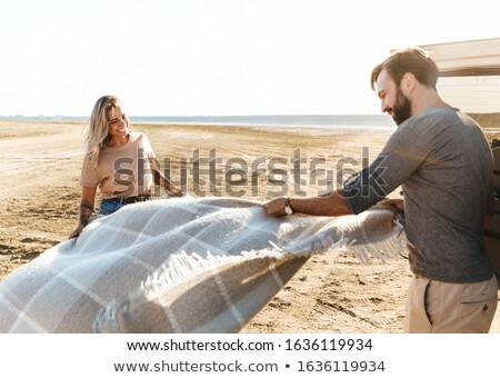 Loving couple outdoors near car with mat litter at the beach. Stock photo © deandrobot