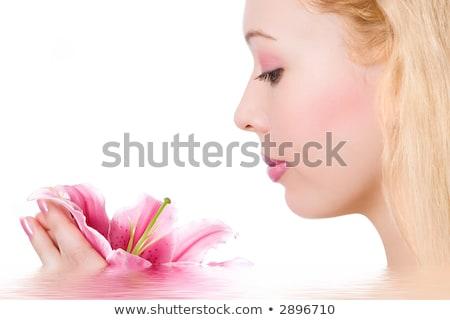 Young blond beauty in spa salon, over rose petals  Stock photo © konradbak