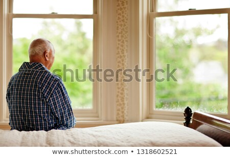 man sitting at the window of an old house Stock photo © meinzahn