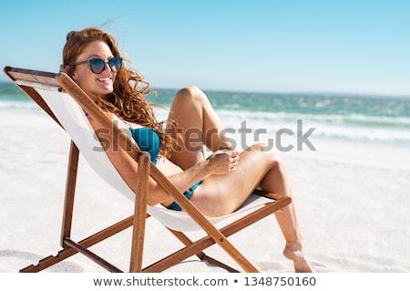 woman in bikini and shades sunbathing on beach Stock photo © dolgachov