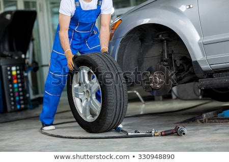 Professional Mechanic in Overalls with New Tire Stock photo © robuart