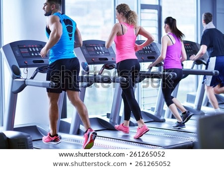young people running on treadmills in modern gym stock photo © boggy