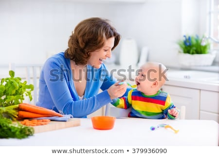 Mother Feeding by Spoon Daughter Sitting on Chair Stock photo © robuart