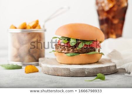 Healthy vegetarian meat free burgers on round chopping board with vegetables and spinach on light ta Stock photo © DenisMArt