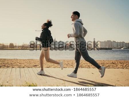 Pár sportok ruházat fut tengerpart fitnessz Stock fotó © dolgachov