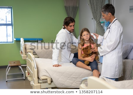Front view of matured Caucasian female doctor using otoscope for checking girl temperature  at hospi Stock photo © wavebreak_media