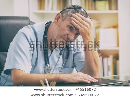 Frustrated Overworked Sad Doctor At Computer Stock photo © AndreyPopov