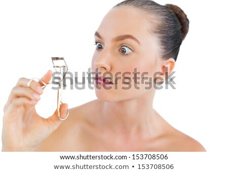 Surprised young woman holding eyelash curler. Stock photo © deandrobot