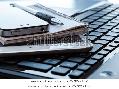 close up of notebook pen and smartphone stock photo © dolgachov