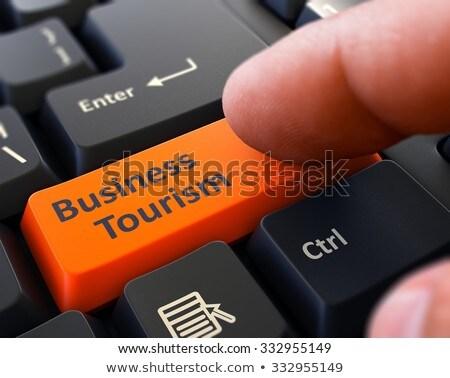 Pressing Orange Button Business Tourism on Black Keyboard. Stock photo © tashatuvango