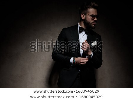 man in tuxedo fixing his bowtie and looks to side Stock photo © feedough